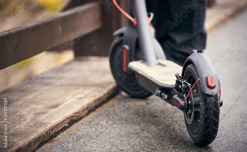 Electric scooter stands on a bridge in the street.