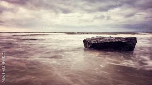 Foto Murales Rock on a beach, peaceful natural background, color toned picture, selective focus.
