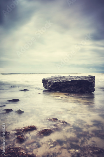 Rock on a beach, peaceful natural background, color toned picture, selective focus.