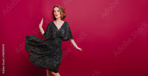 Enchanting slim girl in elegant high heel shoes dancing on claret background. Indoor photo of amazing curly female model in retro black dress having fun in studio.