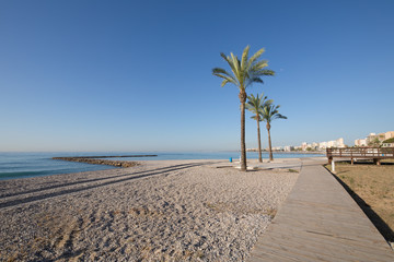 landscape Els Terrers Beach, in Benicassim, Castellon, Valencia, Spain, Europe. Palm trees, wooden walkway, buildings, blue clear sky and Mediterranean Sea