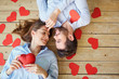 Quadro Couple lying on the wooden floor with hearts view from above. Valentine's Day.