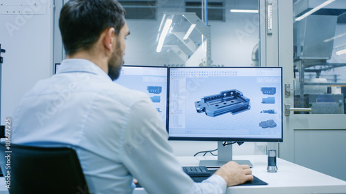 Engineer/ Technician Working on a Personal Computer with Two Displays, He's Designing New Component in CAD Program. Out of the Office Window Components Manufacturing Factory is Seen.