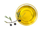 glass bowl of organic olive oil and fres olive with leaves on a white background