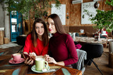 Meeting of girlfriends in cafe. Two fashionable modern girls in red dresses sit and communicate behind a cappuccino cup of coffee. - 186138430
