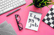 Find dream job. Handwritten motto I love my job in notebook on office desk on pink background top view