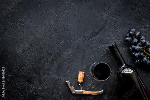 Fototapeta Open the wine. Corkscrew near bottle on black background top view copyspace