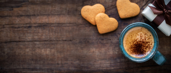 Beautiful Valentine's Day banner with copyspace. Romantic morning with cup of espresso coffee, heart shape cookies and a gift box on rustic wooden table © kuvona