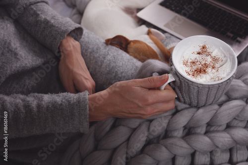 Woman in cozy home clothes relaxing at home, drinking cacao, using laptop. Comfy lifestyle.