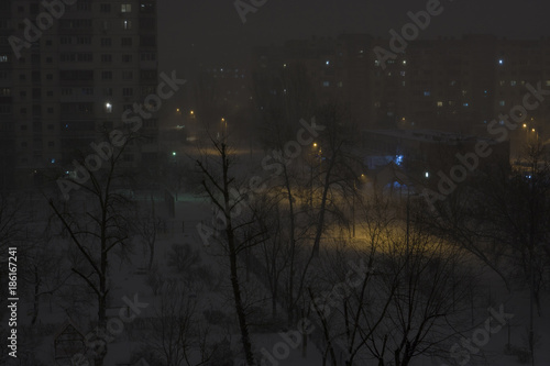 Fotobehang Kiev Night snowy town with buildings and street light. Winter city background