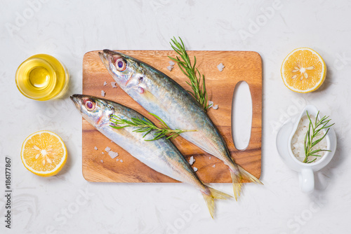 Foto Murales Fish dish cooking with various ingredients. Fresh raw fish decorated with lemon slices and herbs on wooden table.