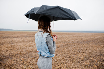 Portrait of brunette curly girl in jeans jacket with black umbrella at field.