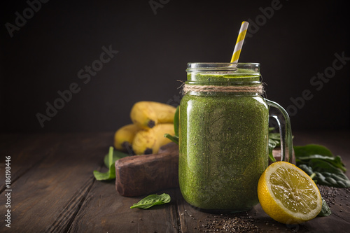 Healthy breakfast with green smoothie in glass jar and ingredients. Detox, diet, healthy, vegetarian food concept with copy space. Dark photo.