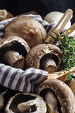 Portobello mushrooms on a black wooden table with  herbs. Selective focus. Copy space. - 186198668