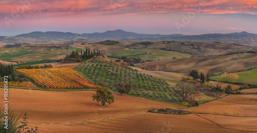 Autumn, panorama in Tuscany, rolling hills, woods and fields on sunset. Rural landscape. Italy, Europe