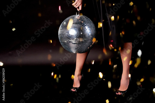 Fototapeta Feet in shoes, dark background. Disco ball. The atmosphere of celebration and dancing