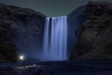 Man exploring Skogafoss waterfall at night under the stars