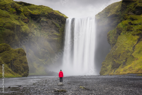 Woman standing near Skogafoss Waterfall in Iceland  - 186211478