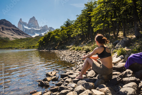 Aluminium Zwart Young female is sitting by the lake in Laguna Capri and admiring the Fitz Roy in Los Glaciares National Park in Patagonia, Argentina.