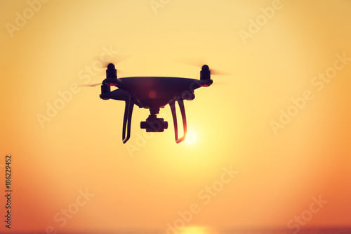 Tuinposter Ochtendgloren silhouette of flying drone which taking photo over sunrise sea