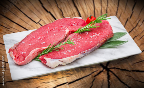 raw steak meat on white dish with tree trunk background - 186229690