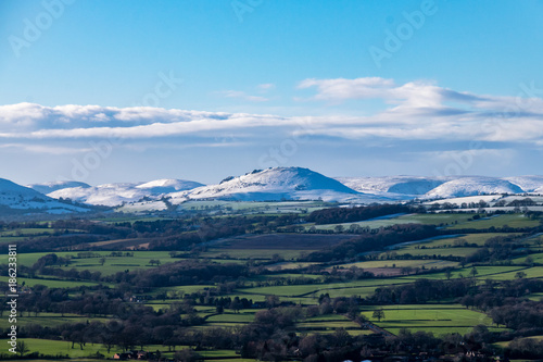 Foto op Plexiglas Blauw Snow covered mountains of Caer Caradoc and the Long Mynd that overlook Church Stretton from Wenlock Edge region, UK