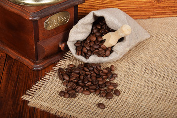 gray bag with roasted seeds of black coffee and an old coffee grinder with free space for text