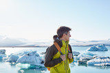 portrait of man in waterproof jacket with orange backpack in Ice Lagoon in Iceland with background of sea and sky. - 186240453