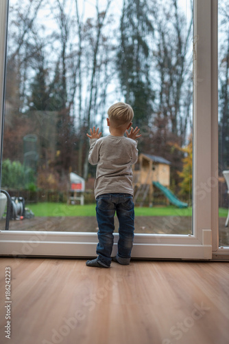 Single blond child standing on a wooden floor at home in front of a window
