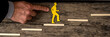 Finger pushing small yellow paper figure climbing steps
