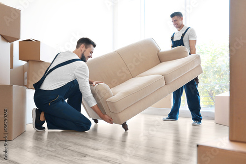 Delivery men moving sofa in room at new home © Africa Studio