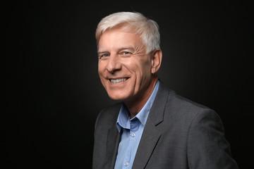 Portrait of smiling mature man on dark background