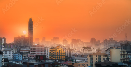 Fotobehang Oranje eclat Sunset cityscape with skyscrapers and slum Bangkok, Thailand