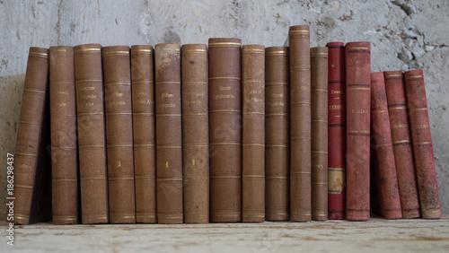 libri antichi vintage appoggiati a muro grezzo