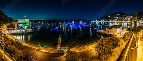 Panoramic view of Avalon City Casino lights and ocean bay full of yachts on Catalina Island at night.