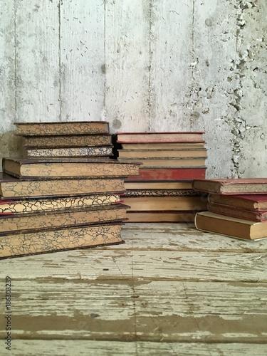 libri antichi impilati su tavolo legno e muro grezzo vintage - 186303239