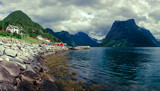 Picturesque scene of Urke village and Hjorundfjorden fjord, Norway. Drammatic sky and gloomy mountains panorama