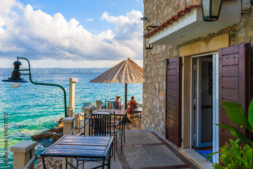 Foto auf Acrylglas See sonnenuntergang BOL PORT, BRAC ISLAND - SEP 8, 2017: Fishing restaurant tables and couple of people having drinks in Bol port at sunset time, Brac island, Croatia.