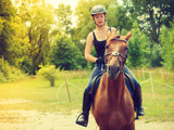 Jockey girl doing horse riding on countryside meadow - 186337876