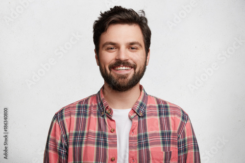 Smiling bearded young male model rejoices coming weekends, dressed casually, isolated over white background. Positive pleased student being in good mood after successfully passed exams at college