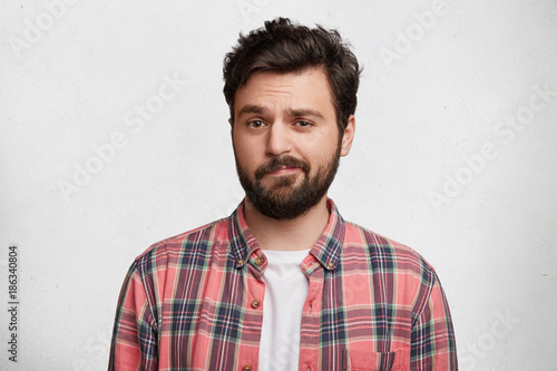 Deurstickers Kapsalon Photo of handsome young man with trendy hairdo and mustache, curves lips and frowns face in bewildermennt, isolated over white concrete background. Attractive male student in casual clothes.