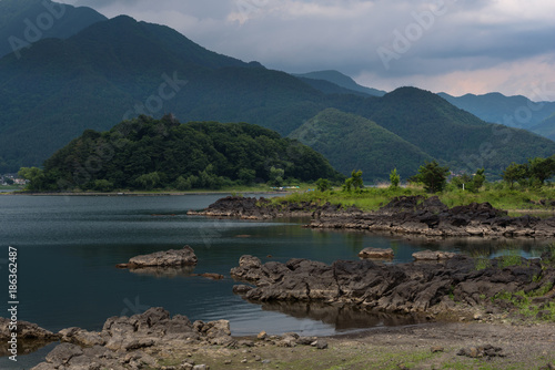 Fotobehang Nachtblauw Rocky volcanic shores of the Kawaguchi lake, Japan