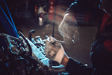 Closeup of an auto mechanic working on a car engine.