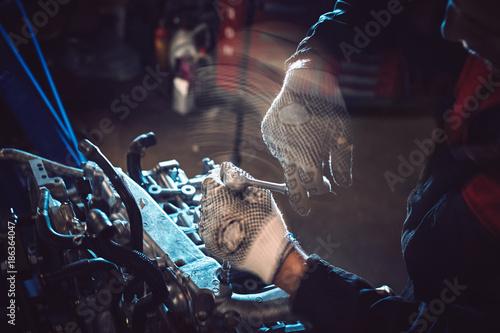 Fototapeta Closeup of an auto mechanic working on a car engine.