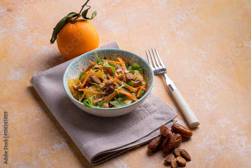 mixed salad with arugula orange carrots almond and date - 186365889