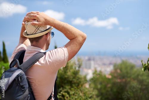 Poster Traveler in sunhat is enjoying a beautiful view.