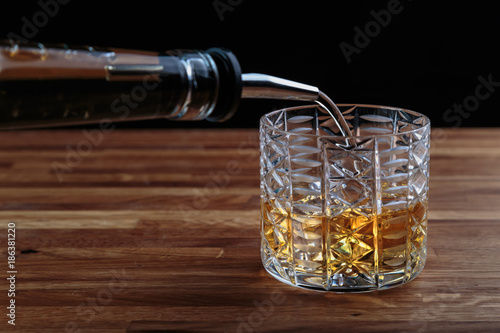 whiskey is poured into a crystal glass with ice standing on the oak surface of the table