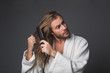 Waist up portrait of mature male in white robe taking care about his long hair. Isolated on grey background