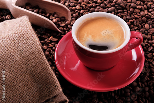 Red coffee cup with espresso and roasted beans
