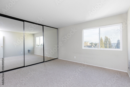 Bedroom empty, with mirror closet and new carpet for virtual staging.